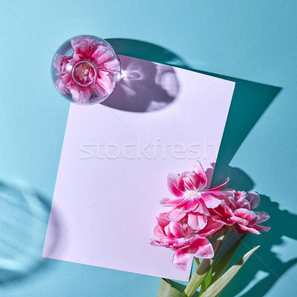 Beautiful spring composition with a postcard decorated with tulips on a blue background. Flat lay. Stock photo © artjazz