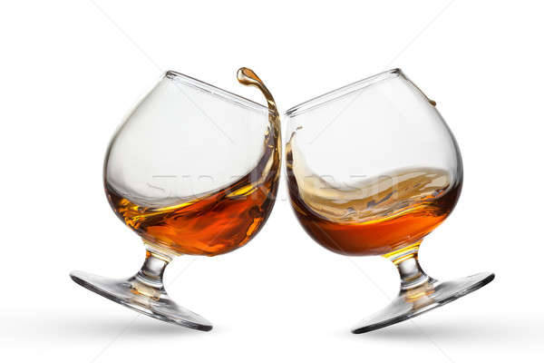 Splash of cognac in two glasses isolated on white background Stock photo © artjazz
