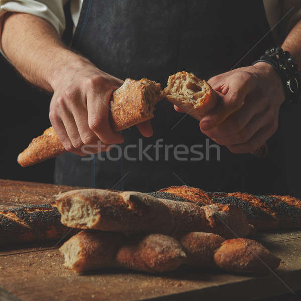 Male hands break the baguette Stock photo © artjazz