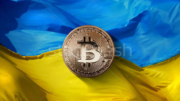 bitcoin Gold on a Ukrainian flag background. Ukraine, successfully developing country in the crypto  Stock photo © artjazz