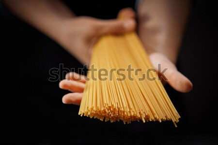 A yellow paste in the hands of a woman, on a dark background. Stock photo © artjazz