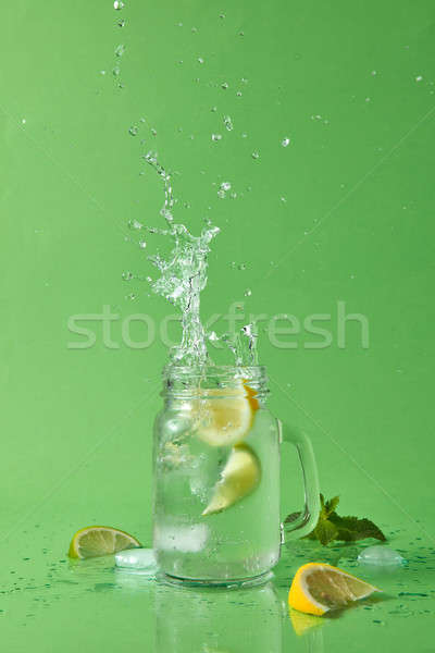 Cocktail splash from ice cube in the glass jar. Drops of liquid and pieces of lemon and lime on a gr Stock photo © artjazz