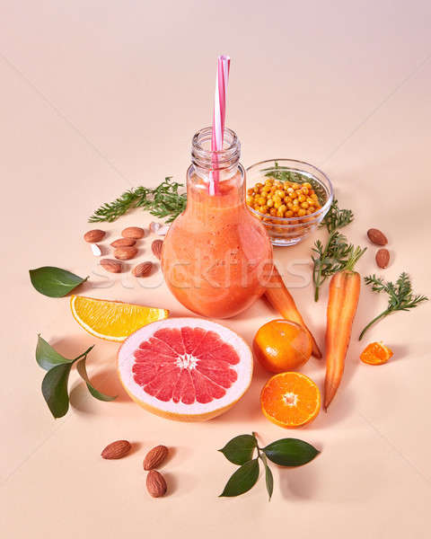 Healthy breakfast ogange smoothie from citrus fruits, sea buckthorn, carrot, almonds in a glass bowl Stock photo © artjazz