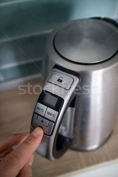 man hand click on the button iron electric kettle on the background of the kitchen Stock photo © artjazz