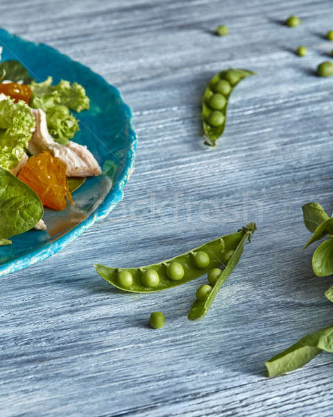 Freshly picked green peas and the part of blue ceramic plate with salad on a gray wooden table with  Stock photo © artjazz