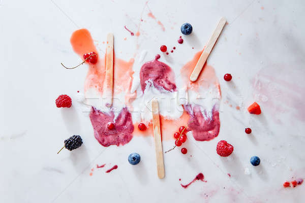 Bright pattern of splashes of ice cream of different fresh berries and sticks on a gray marble backg Stock photo © artjazz