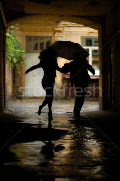 silhouette of couple with umbrella running from rain Stock photo © artjazz