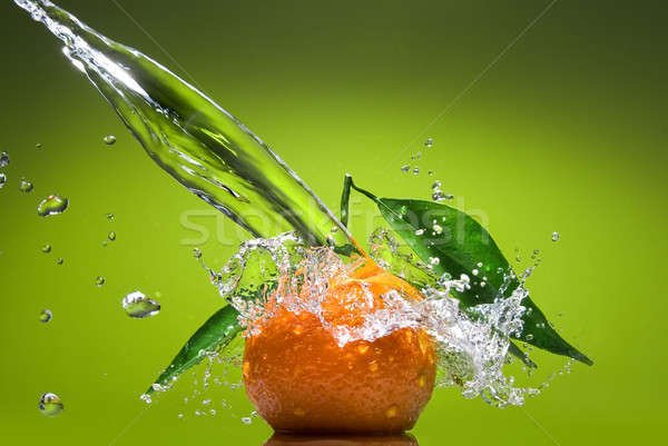 Tangerine with green leaves and water splash on green background Stock photo © artjazz