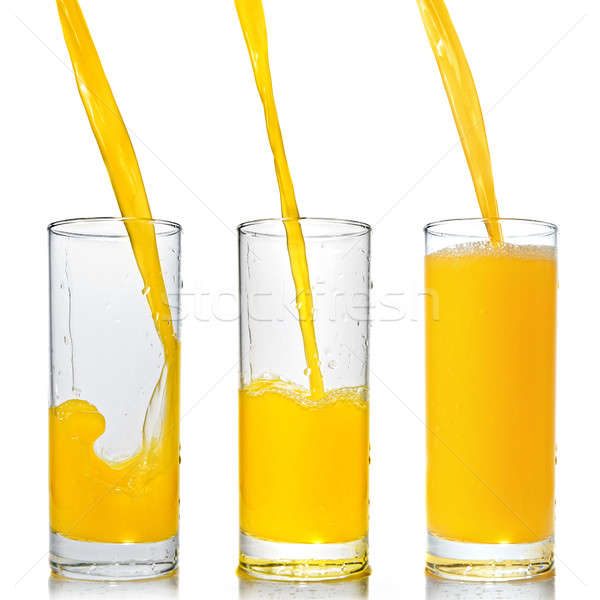 orange juice poring into glass isolated on white Stock photo © artjazz