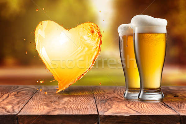 Love beer. Beer in glass with heart splash on wooden table again Stock photo © artjazz