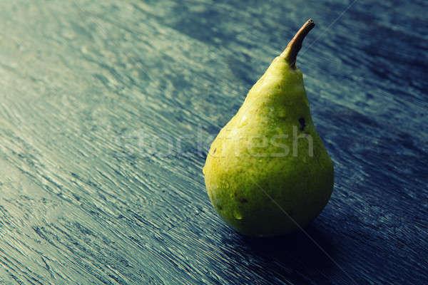 Green pear on a dark background Stock photo © artjazz