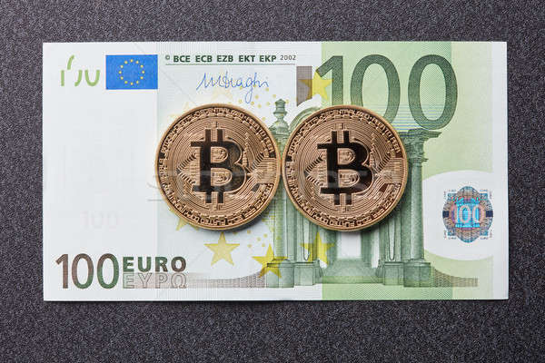 Gold coins bitcoin and one hundred euro banknote on a dark background Stock photo © artjazz
