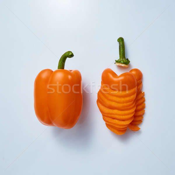 Yellow pepper half and chopped into pieces on gray background Stock photo © artjazz