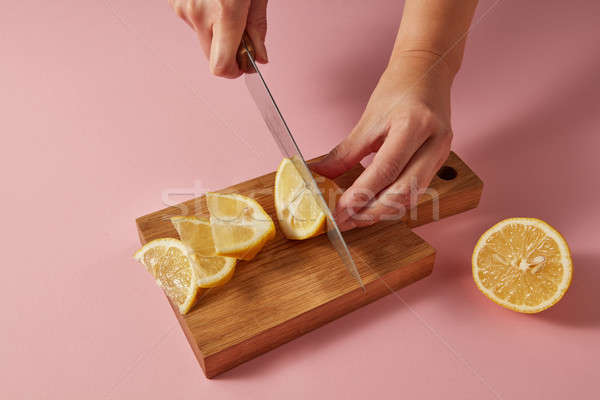 Citrus fruit natural lemon on cutting board. Female hands cutting a yellow ripe lemon on half on a w Stock photo © artjazz