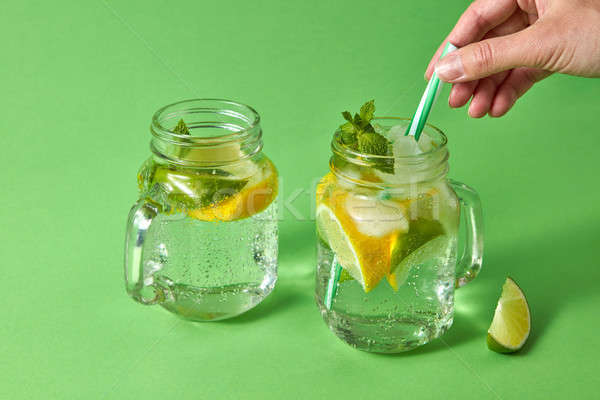 A woman's hand inserts plastic straw into a glass jar with lemonade from natural ingredients - water Stock photo © artjazz
