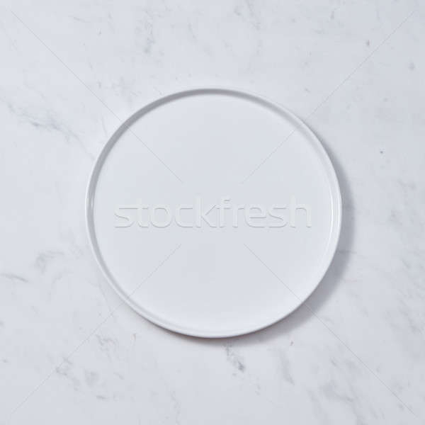 Decorative ceramic white plate, covered with glazed on a gray background. Traditional ceramic handcr Stock photo © artjazz