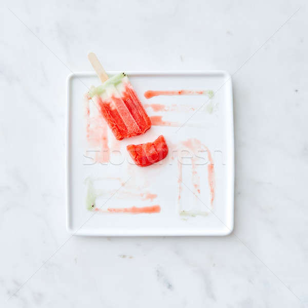 Broken fruit ice cream lolly on a white plate with a pattern from the thawing ice cream on a gray ma Stock photo © artjazz