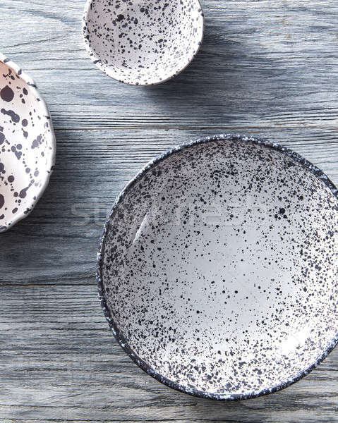 Set of handcrafted porcelain bowls on a gray wooden table. Vintage painted plates dishes. Flat lay. Stock photo © artjazz