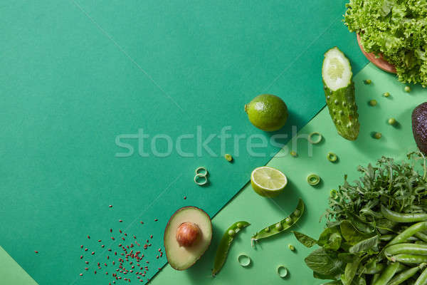 Freshly picked greens for salad - lettuce, green pea sticks, rosemary, avocado, lime, cucumber on a  Stock photo © artjazz