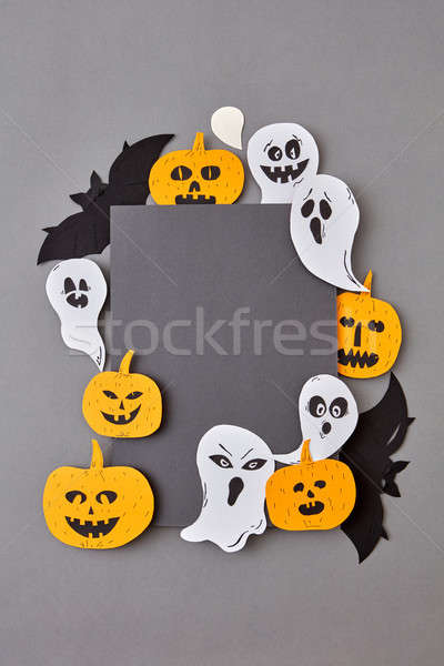 Handcraft paper greeting card with flying ghosts and spirits and yellow scary pumpkins, bats on a gr Stock photo © artjazz