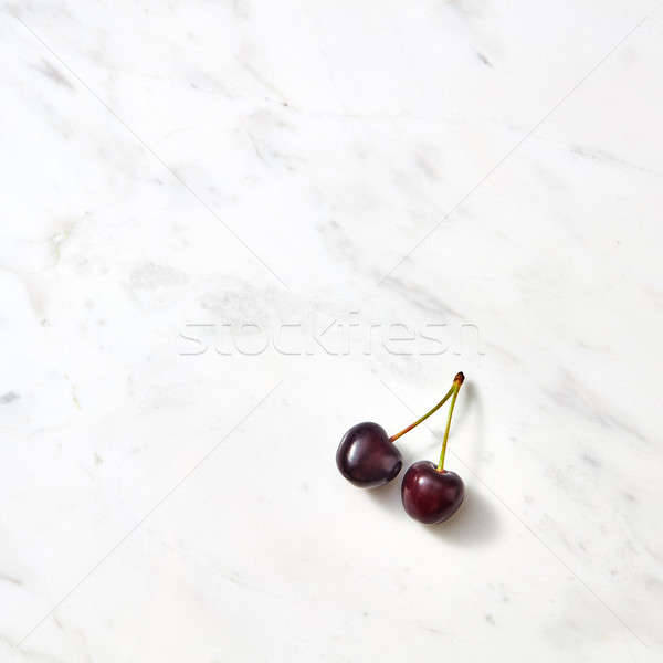 Red sweet cherries on a marble background with copy space. Stock photo © artjazz