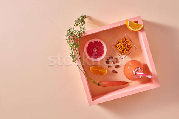 Citrus vegetable smoothies with berries and nuts in a glass on an orange paper background in square  Stock photo © artjazz