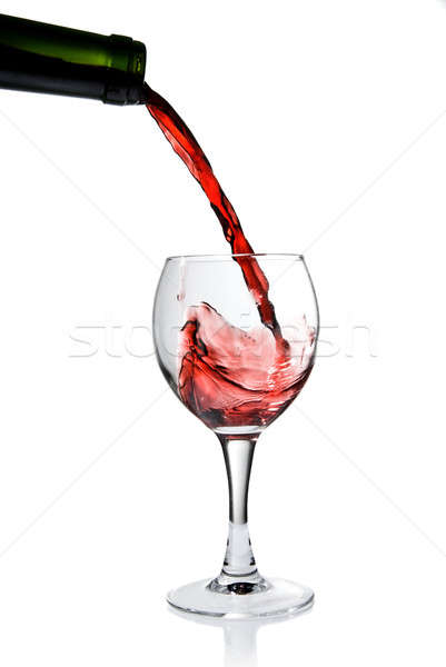 Pouring red wine in goblet isolated on white Stock photo © artjazz