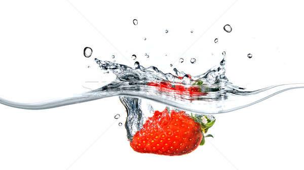 Fresh strawberry dropped into blue water with splash Stock photo © artjazz