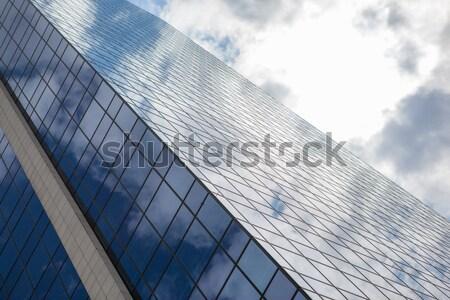 Modern füstölt üveg irodaház kék felhős Stock fotó © artjazz