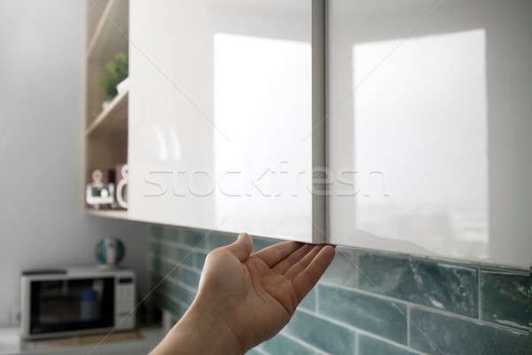 male hand open the cupboard doors in the kitchen Stock photo © artjazz