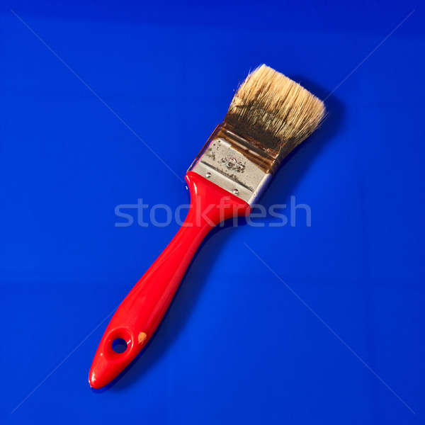 Paint brush for apartment repair isolated on a blue . Stock photo © artjazz