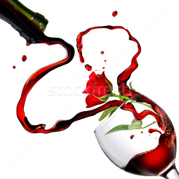 Heart from pouring red wine in goblet with red rose isolated on white Stock photo © artjazz