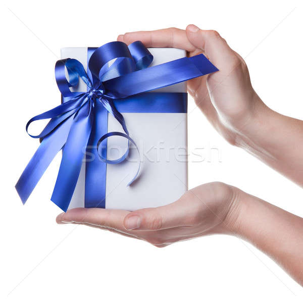 Hands holding gift in package with blue ribbon isolated on white Stock photo © artjazz