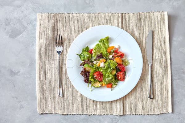 Salad of vegetables and cheese in a plate with a knife and fork on a gray background Stock photo © artjazz