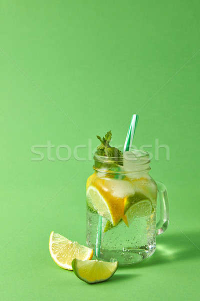 Stock photo: Mason jar with homemade sparkling lemonade with ice, slices of lime and lemon, leaf of mint with pla