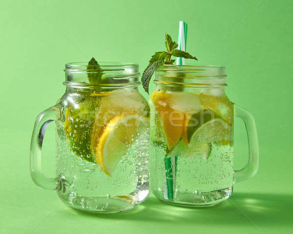 Cold natural alcoholic mojito with bubbles of air. Two glass mason jar with handmade cocktail on a g Stock photo © artjazz