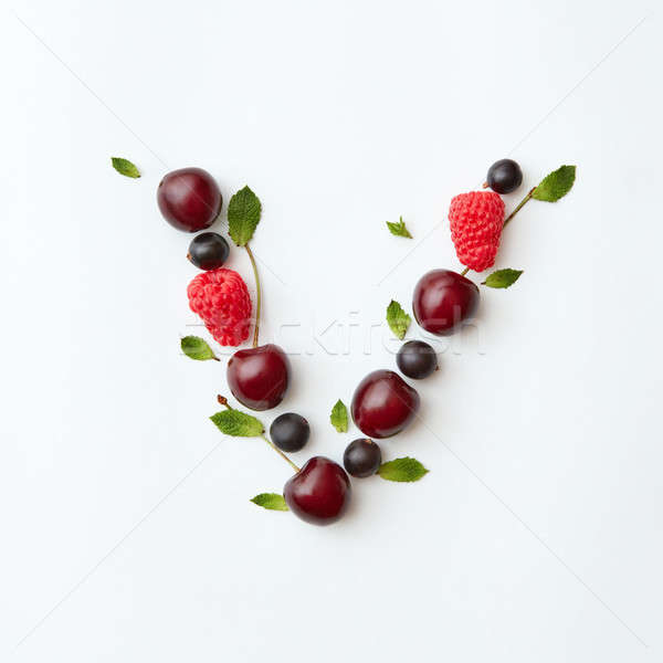 Berries organic pattern of letter V english alphabet from natural ripe berries - black currant, cher Stock photo © artjazz