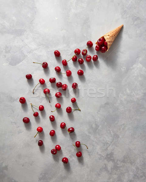 Sweet fresh cherries are poured from a waffle horn on a gray sto Stock photo © artjazz