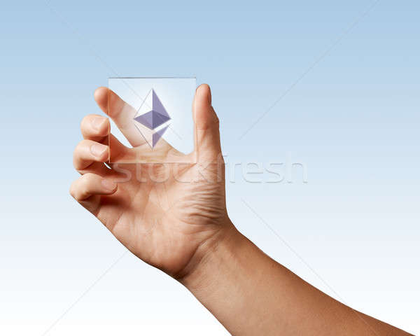 Icon of etereum on a digital screen man holds on a blue background Stock photo © artjazz