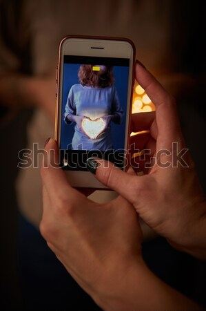 Female hands with a phone there is a photo with a girl holding a heart from Christmas lights Stock photo © artjazz