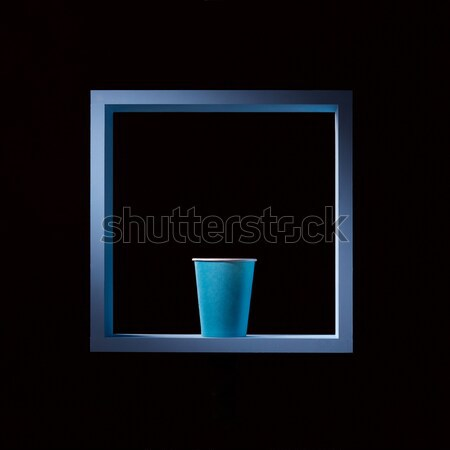 Blue paper cup in a blue square frame on a black square background. Symmetrical central composition. Stock photo © artjazz