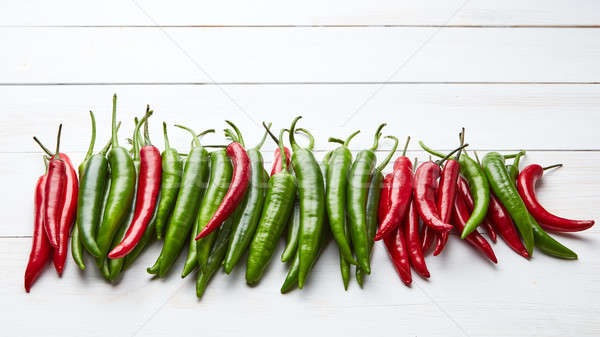 a colorful mix of the freshest and hottest chili peppers on wooden table Stock photo © artjazz