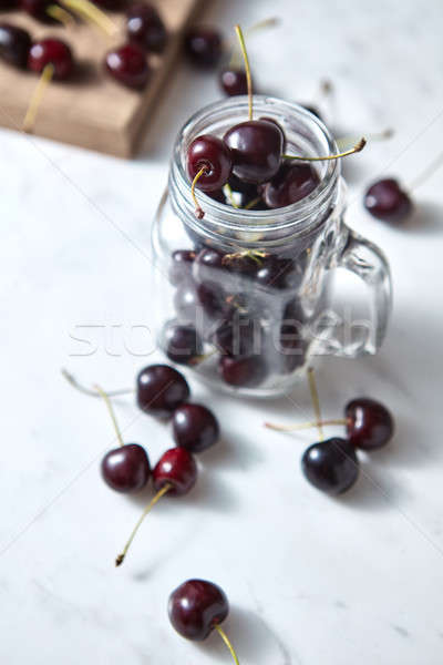 Close-up ripe sweet cherry in the glass cup, on a wooden board on white background with soft focus. Stock photo © artjazz