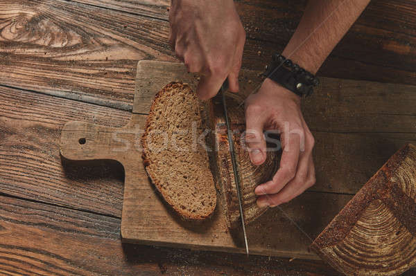 fresh bread cut man's hands on wooden board Stock photo © artjazz