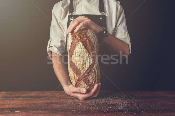 Baker's hands hold an oval bread. Stock photo © artjazz