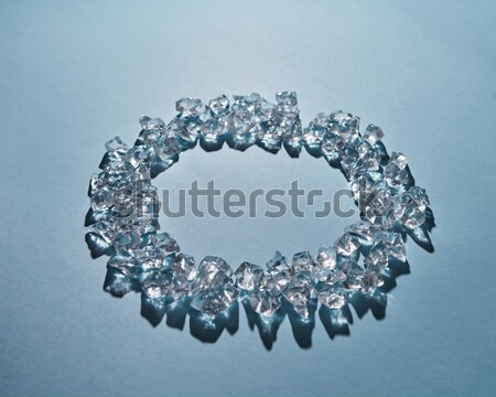 Cubes of cold ice in the form of a round frame on a blue background. Flat lay Stock photo © artjazz