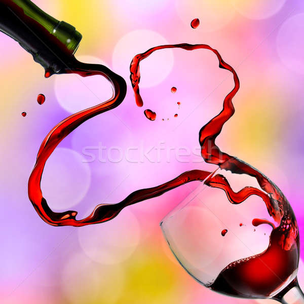 Heart from pouring red wine in goblet on color background Stock photo © artjazz