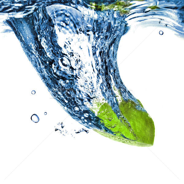 Fresh lime dropped into blue water isolated on white Stock photo © artjazz