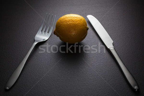 lemon with knife and fork on black Stock photo © artjazz