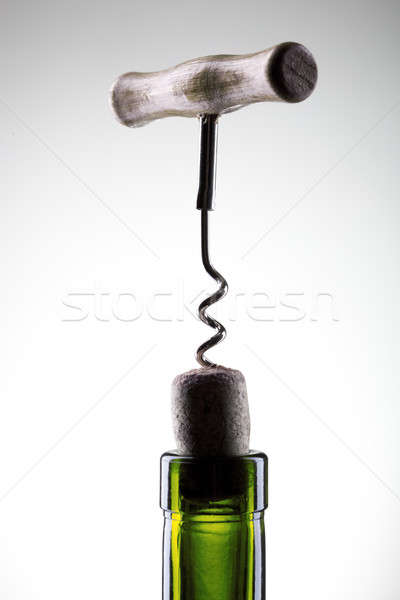 Corkscrew inserted into a wine fuse in a bottle on white Stock photo © artjazz